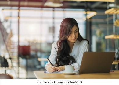 Geschäftsfrau arbeitet an einem Computer und schreibt Notizblock im Büro.