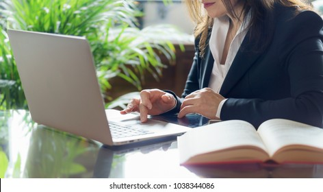 Business woman working on a laptop. Business, legal law, advice and justice concept. Selective focus.