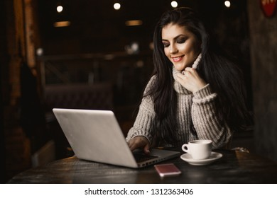 Business woman working on a laptop and drinking coffee in a cafe.