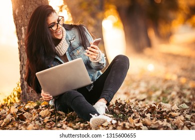 Business woman working on a laptop sitting in the park.