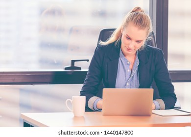 Business woman working on laptop in modern office with city background.