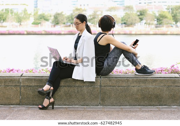 Business woman working on the laptop computer sitting near the relaxing sport woman in city park, Life balance concept, Workaholic and healthy lifestyle.