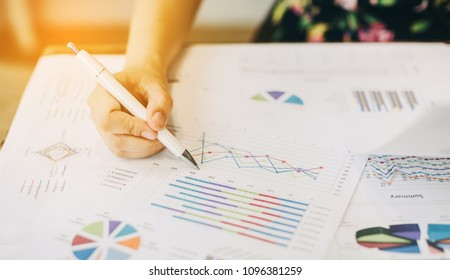 business woman working on project for analyzing company financial report balance statement with documents graphics at modern office space. Concept picture of business,economy, market,money and tax.