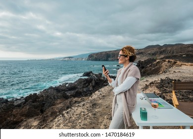 Business woman working outdoor in total freedom in front of the ocean with a desktop and notebook and mobile phone - concept of digital nomad and fre lifestyle from usual office - alternative people