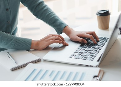 Business woman working and typing on laptop computer on the table.