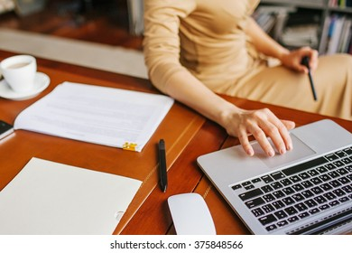 Business woman works on laptop and cup of coffee and papers out of focus