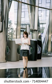 Business woman works on a laptop. Office center. Young office worker. Work on the financial exchange. Translator.