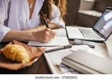Business woman writes at diary and laptop, papers croissant out of focus
