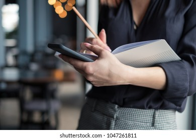 Business woman writes in her diary and holds a mobile phone