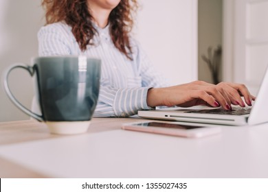 A business woman writes on her laptop placed on top of a table. Wears work clothes. Next to the laptop it has a cup of coffee and the mobile. In a homogeneous environment with white walls