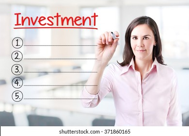 Business woman writing blank Investment list. Office background.