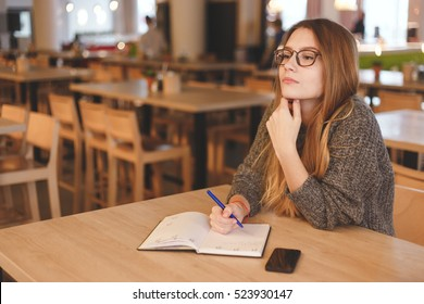 Business woman writing to do list in a cafe