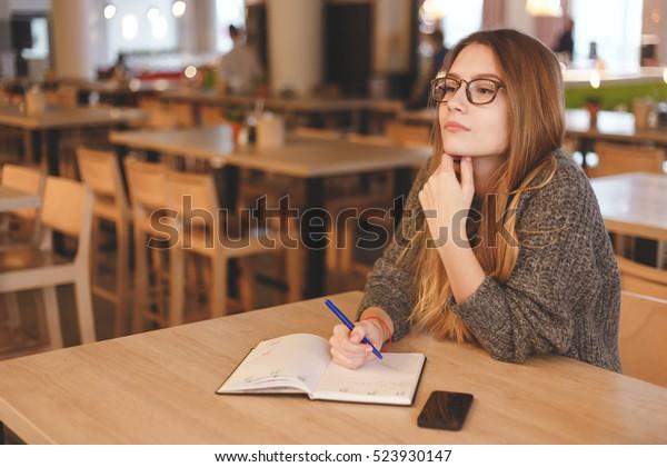 Geschäftsfrau, die in einem Café eine Liste schreibt
