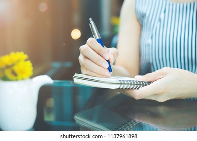 Business woman writing on a notebookwith a pen in the office