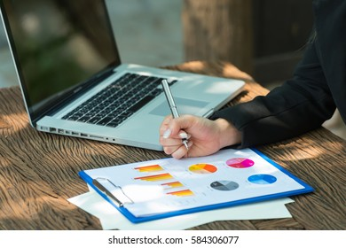 Business woman is writing on business paper with computer notebook