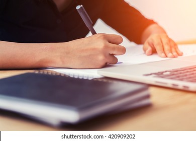 Business Woman Writing with pen in notepad on workplace.