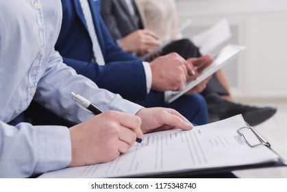 Business woman writing in resume while waiting for interview sitting in row