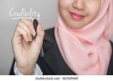 Business woman writing text :Credibility over gray background