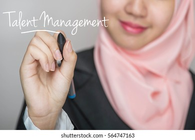 Business woman writing text : Talent Management over gray background