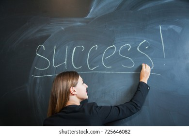 Business woman writing the word success on desk. Female office worker put down text on black board