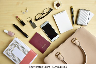 Business woman's everyday-life travel accessories flat lay on light wooden background with formal beige handbag, a book, cellphone, blank notepad, luxury pen, business card, glasses, cosmetics