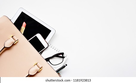 Business woman's everyday-life travel accessories flat lay on light wooden background with formal beige handbag, a cellphone, blank notepad, luxury pen, glasses and lipstick with copy space for text
