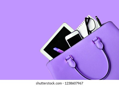 Business woman's everyday-life travel accessories flat lay on light purple background with formal light purple handbag, a cellphone, blank notepad, luxury pen, glasses and lipstick, copy space