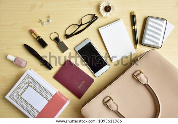軽い木の背景にビジネスマンの日常の旅行アクセサリーが平らに置かれ、正式なベージュのハンドバッグ、本、携帯電話、空のメモ帳、高級ペン、名刺、眼鏡、化粧品