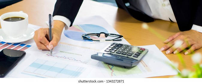 Business women analyze documents presentation shareholders' meeting,with charts and marketing plan graphs,pen in hand,coffee mug,calculator,smartphone,banner panoramic horizontal for header
