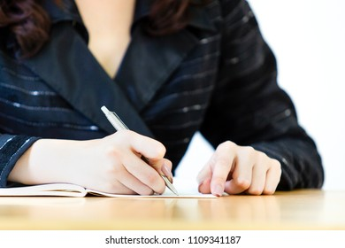 Business women in black suit writing in a notebook close up on her hands.