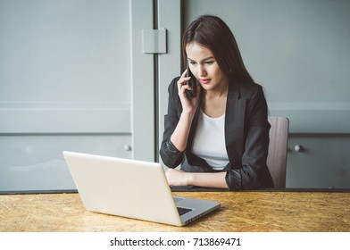 Business women are contacting customers by phone while working in her office