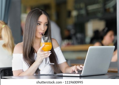 Business women drinks juice and works on computer at cafe