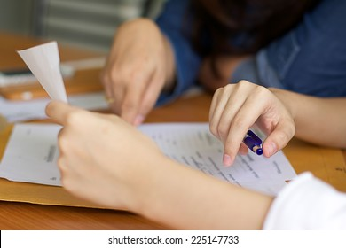Business women filling out paperwork for agreement