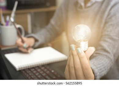 Business women hand holding light bulb, concept of new ideas with innovation and creativity.