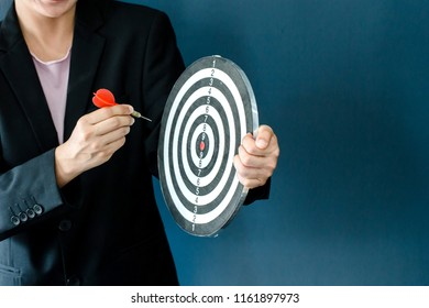 business women hand holding a target with three darts hitting the center over blue background. Concept of personal coaching success