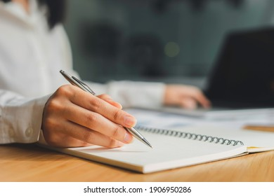 Business women hand And notepads placed on the table in the office, writing ideas And taking notes