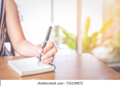 Business women hand writing on a notepad with a pen on a wooden desk in a office.