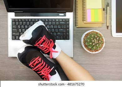 Business women laying her legs in sport shoes over the laptop, Life and work balance concept. (Lighting effect)