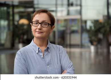 Business women portrait. Middle aged woman wearing glasses and standing in the office and looking straight at the camera. Head shot of employee, office worker, entrepreneur or customer service.