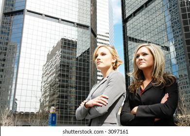 business women posing in front of a skyscraper in downtown denver