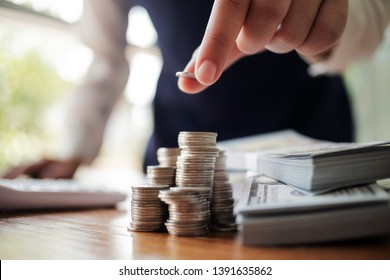 Business women put coin stack money and many bank note in office, Save money for future and Retirement.