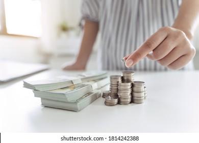 Geschäftsfrauen stellen Münzgeld und viele Banknoten im Amt, sparen Geld für die Zukunft und für das Ruhestand.