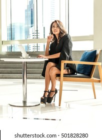 Business women sitting on wood chair while is sitting in skyscraper building,She thinking about project, laptop put on the modern table.She wear black suit.