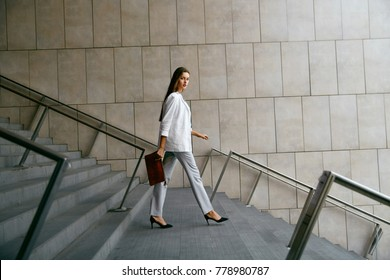 Business Women Style. Woman Going To Work Walking Downstairs. Portrait Of Beautiful Smiling Female In Stylish Office Clothes Going Down Stairs. High Resolution.