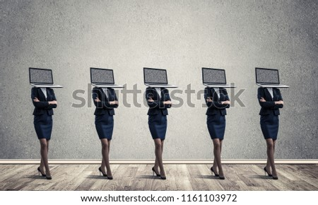 Business women in suits with laptops instead of their heads keeping arms crossed while standing in a row in empty room with gray wall on background.
