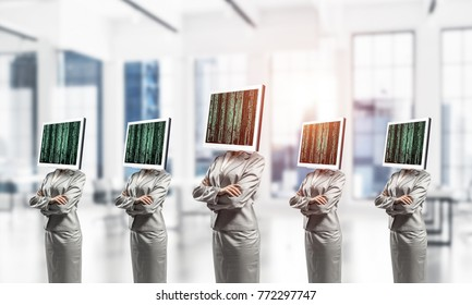 Business women in suits with monitors instead of their heads keeping arms crossed while standing in a row inside office building.