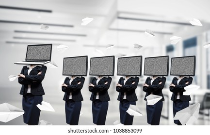Business women in suits with TV instead of their heads keeping arms crossed while standing in a row and one at the head with laptop inside office building.