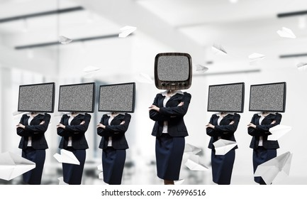 Business women in suits with TV instead of their heads keeping arms crossed while standing in a row and one at the head with old TV inside office building.
