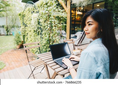 Business women use laptop rear view sitting on bench in cafe, Business communication