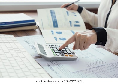 business women using a calculator to calculate the numbers for audit and evaluation performance. finance accounting concept
